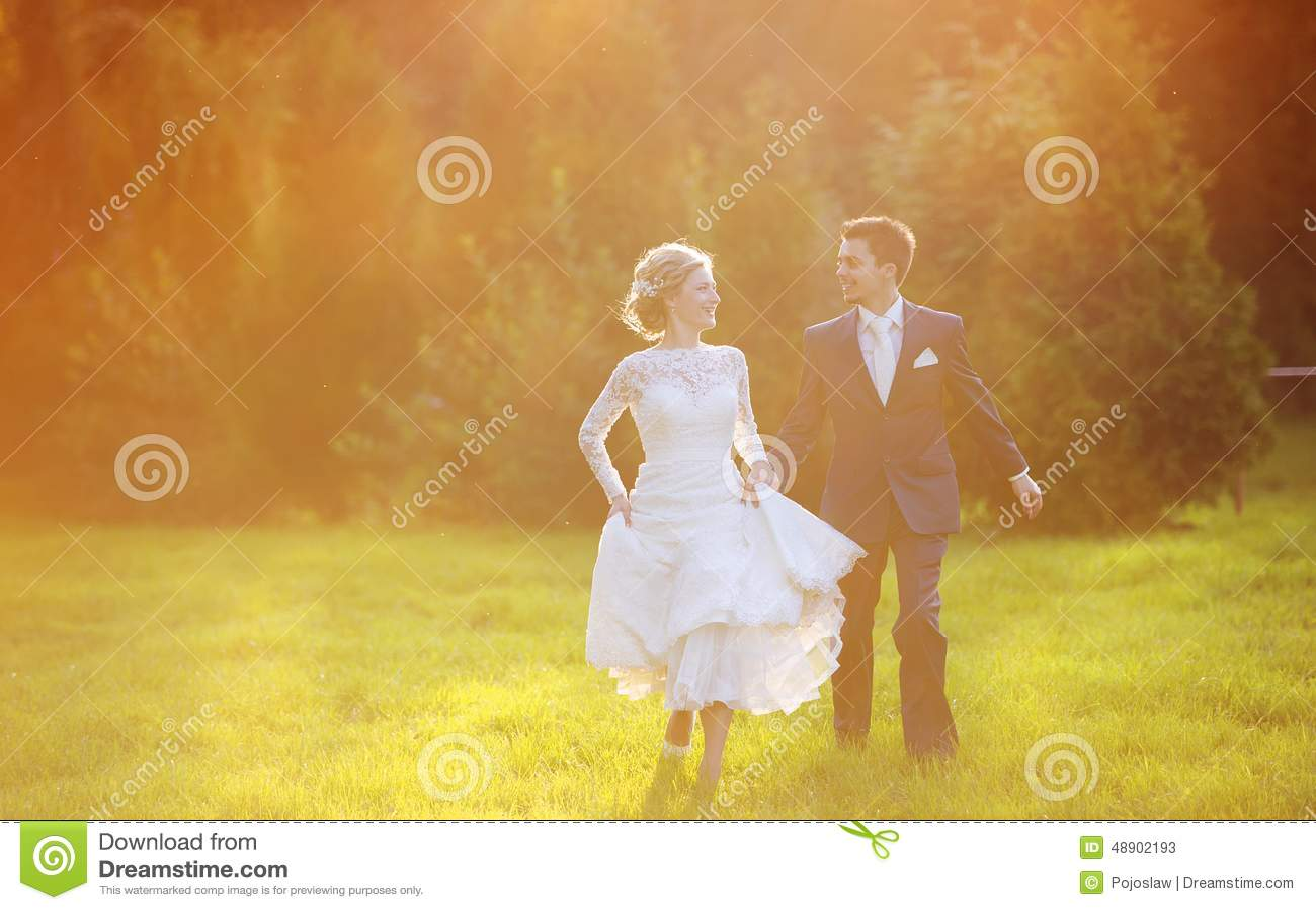 Pares jovenes de la boda en prado del verano
