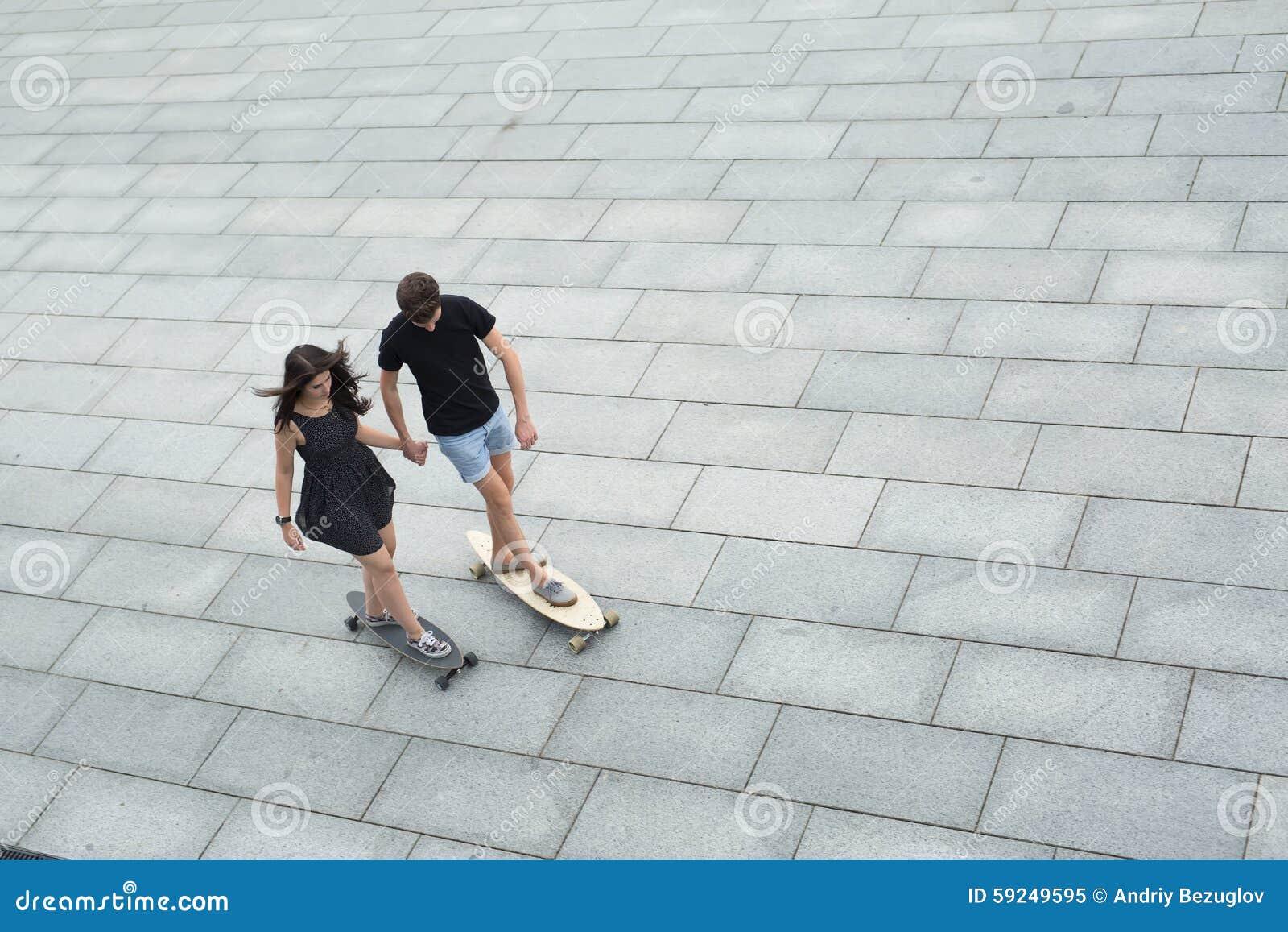 Pares jovenes de longboards elegantes del paseo de los adolescentes