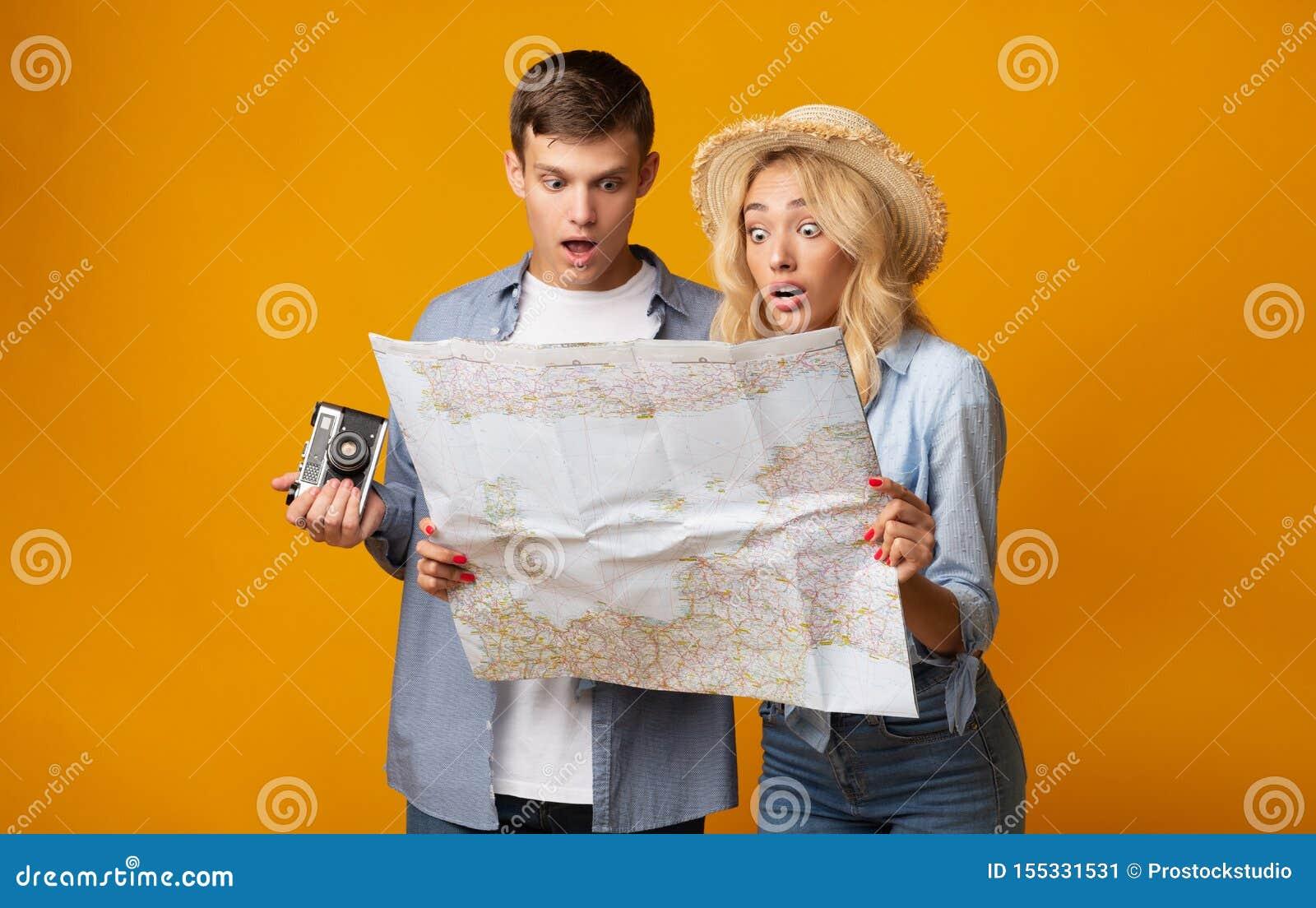 Pares jovenes de los turistas que sostienen un mapa que es chocado