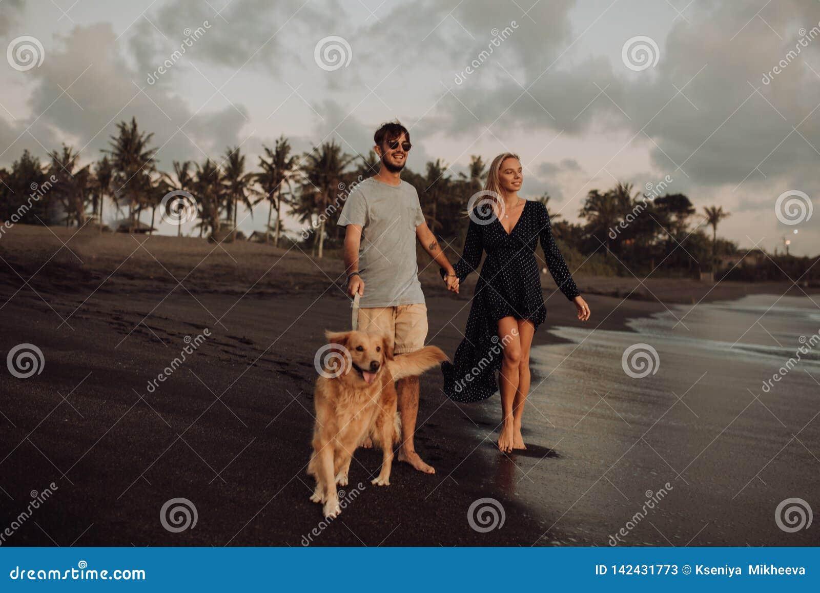 Pares jovenes del inconformista de la risa feliz hermosa con golden retriever en la playa océano una arena Ondas concepte de la l