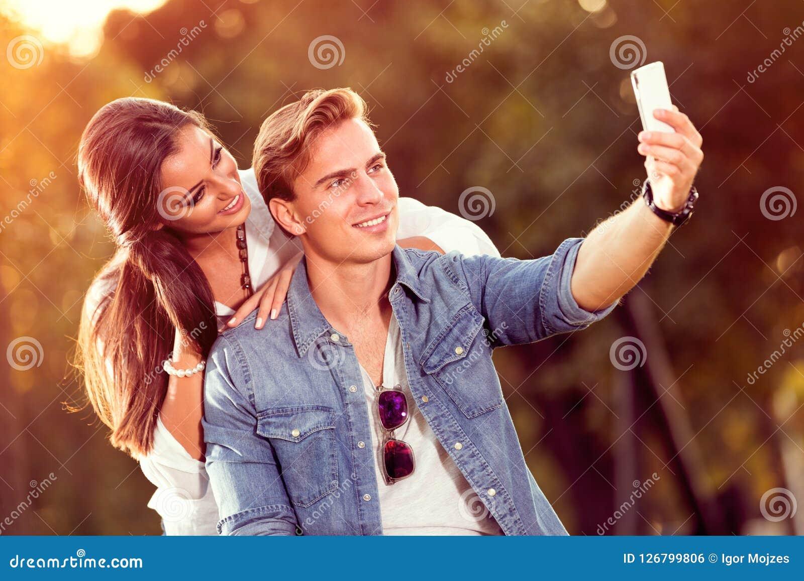 Pares jovenes del otoño que hacen el selfie