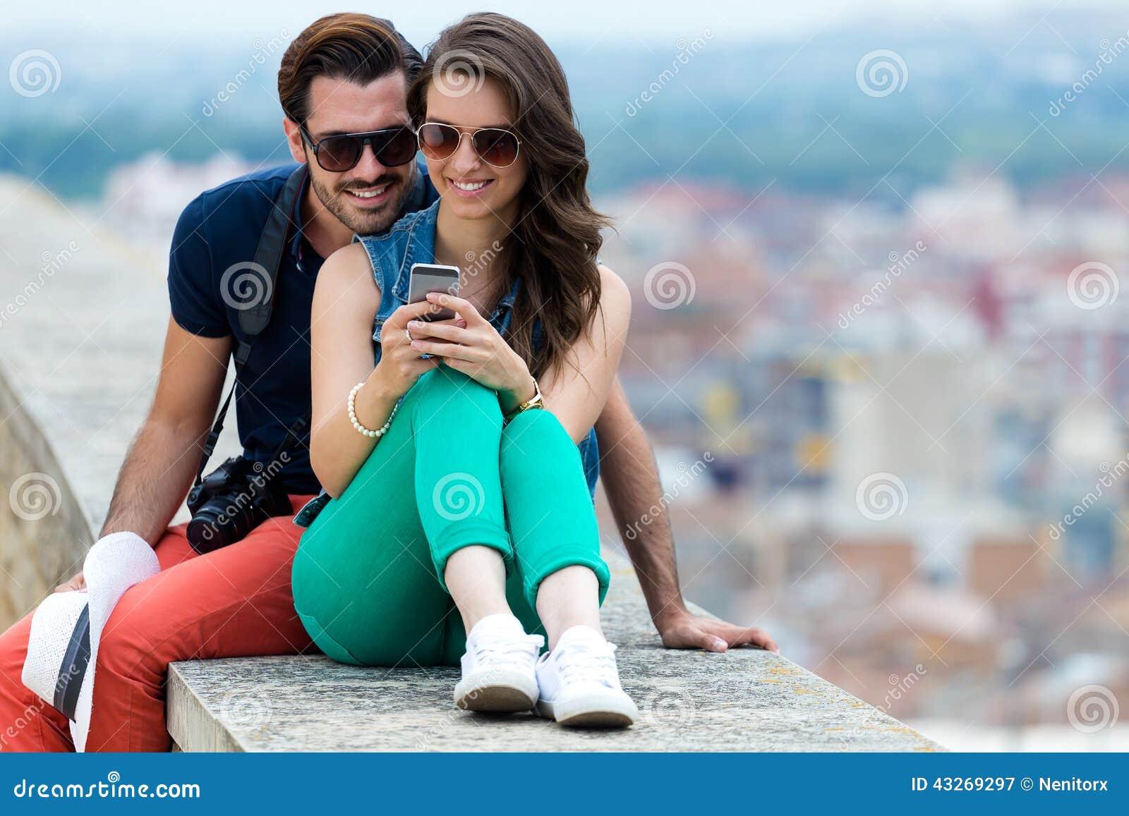 Pares jovenes del turista en ciudad usando el teléfono móvil