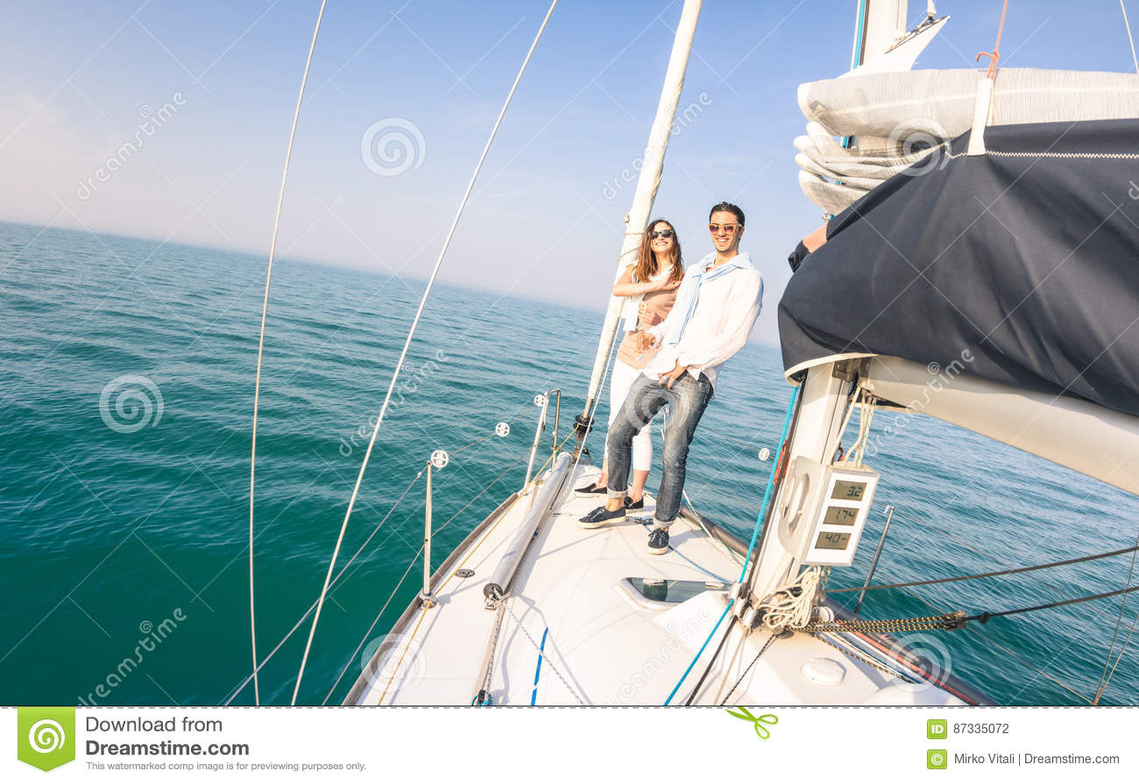 Pares jovenes en amor en el barco de vela que se divierte con champán