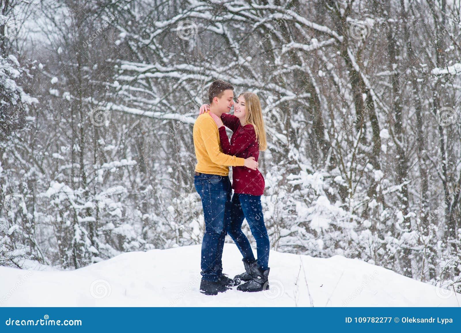 Pares jovenes en bosque del invierno