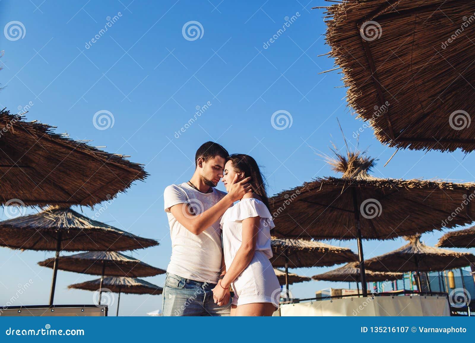 Pares jovenes en el amor que abraza entre los paraguas de lámina en la playa del mar