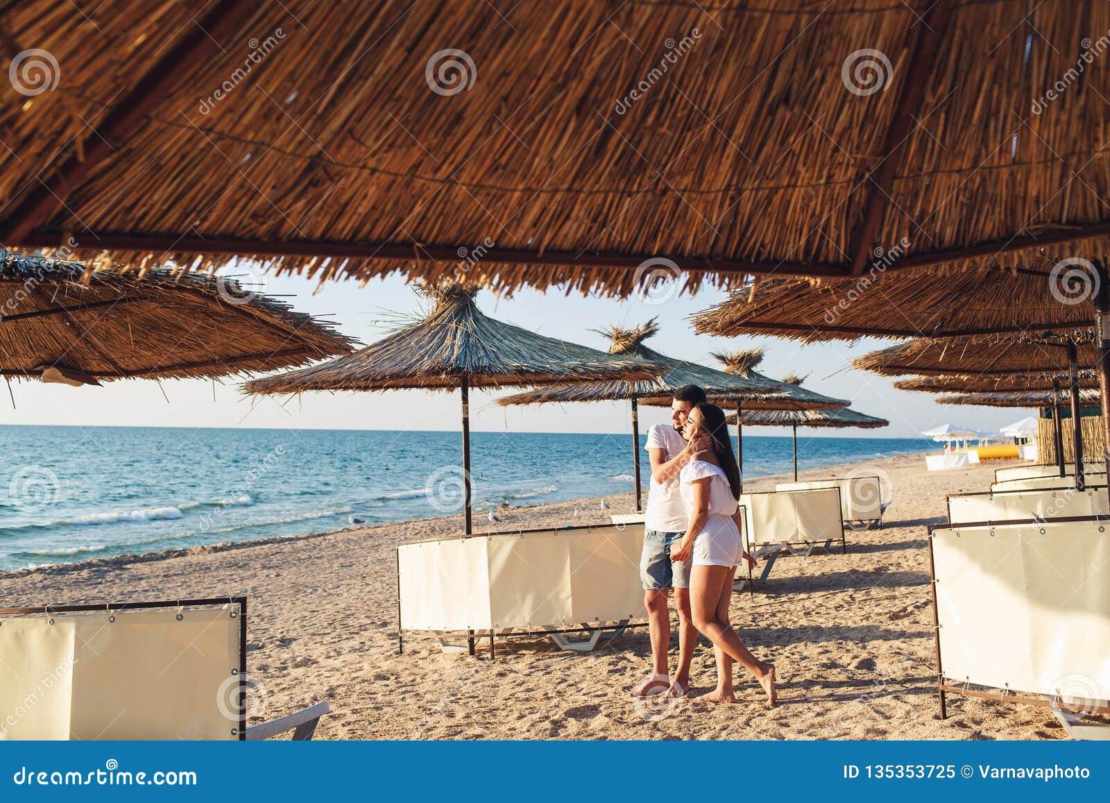 Pares jovenes en el amor que lleva a cabo las manos entre los paraguas de lámina en la playa del mar