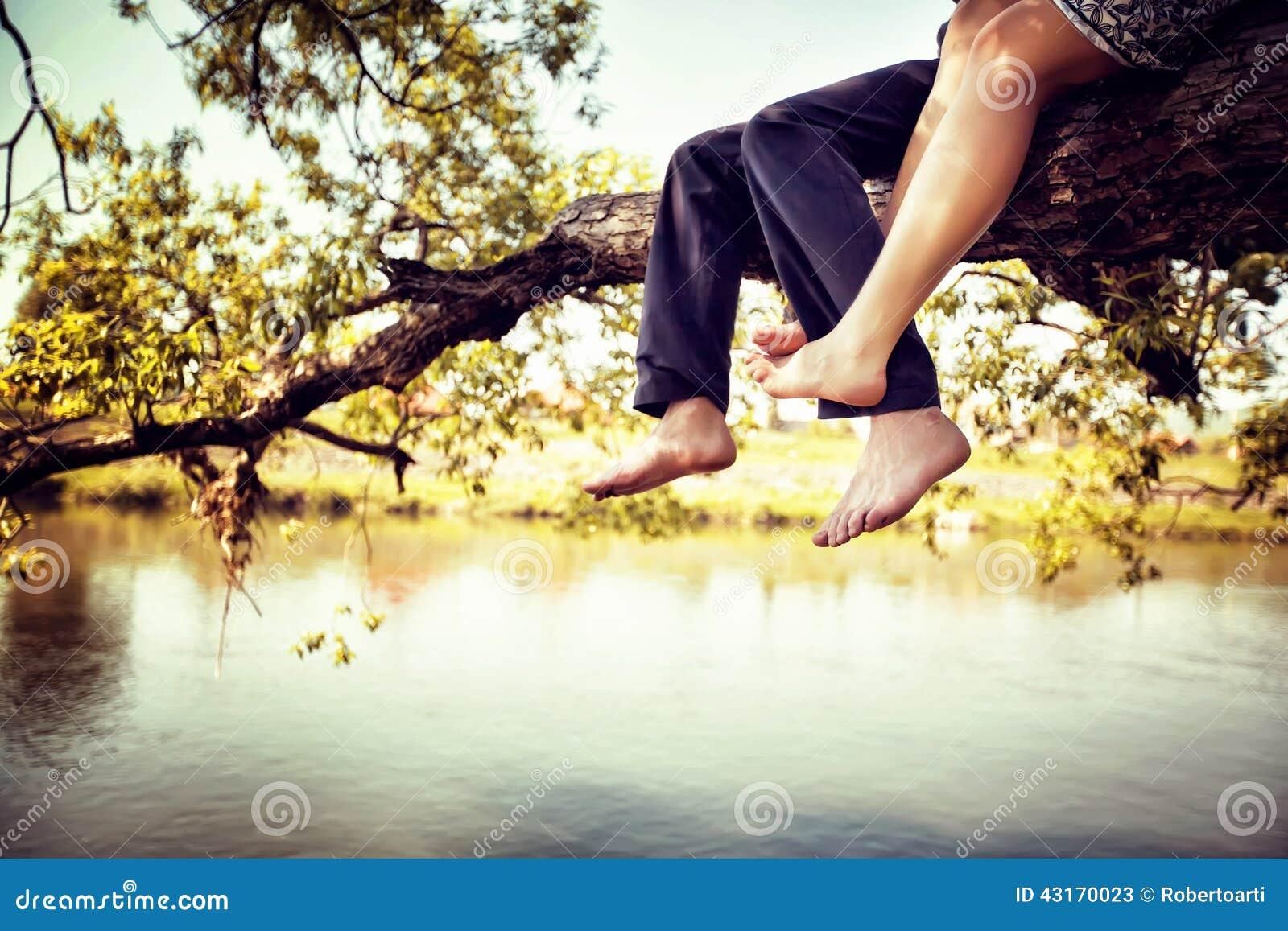 Pares jovenes en el amor que se sienta a piernas cruzadas en una rama de árbol sobre el río en día soleado agradable