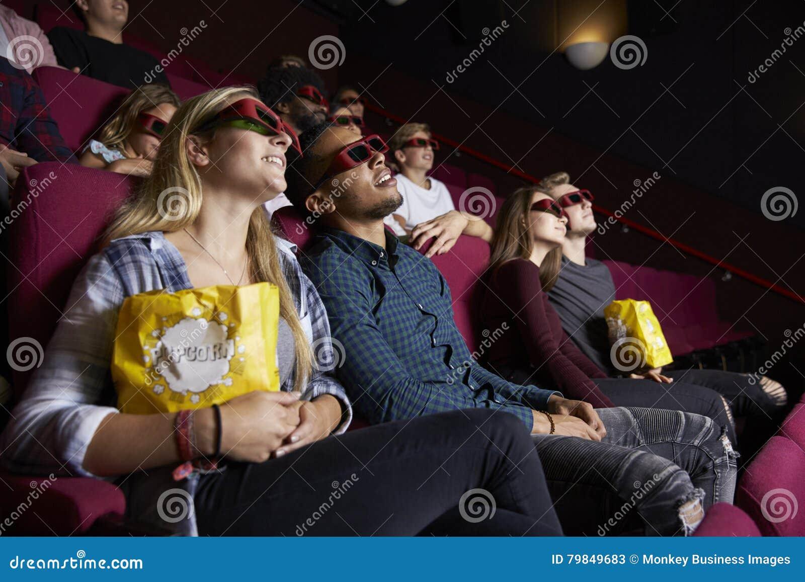 Pares jovenes en el cine que lleva los vidrios 3D que miran la película