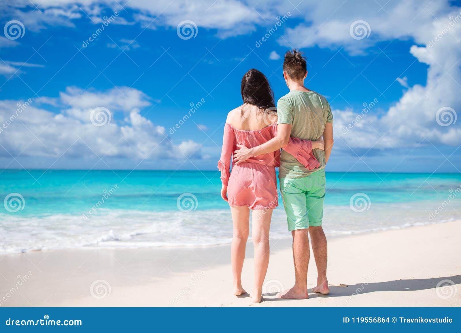 Pares jovenes en la playa blanca durante vacaciones de verano La familia feliz disfruta de su luna de miel