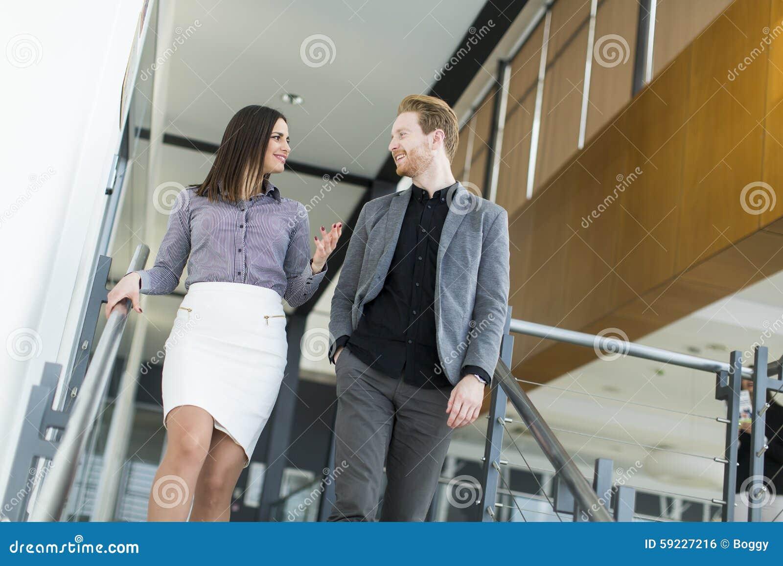 Pares jovenes en las escaleras en oficina