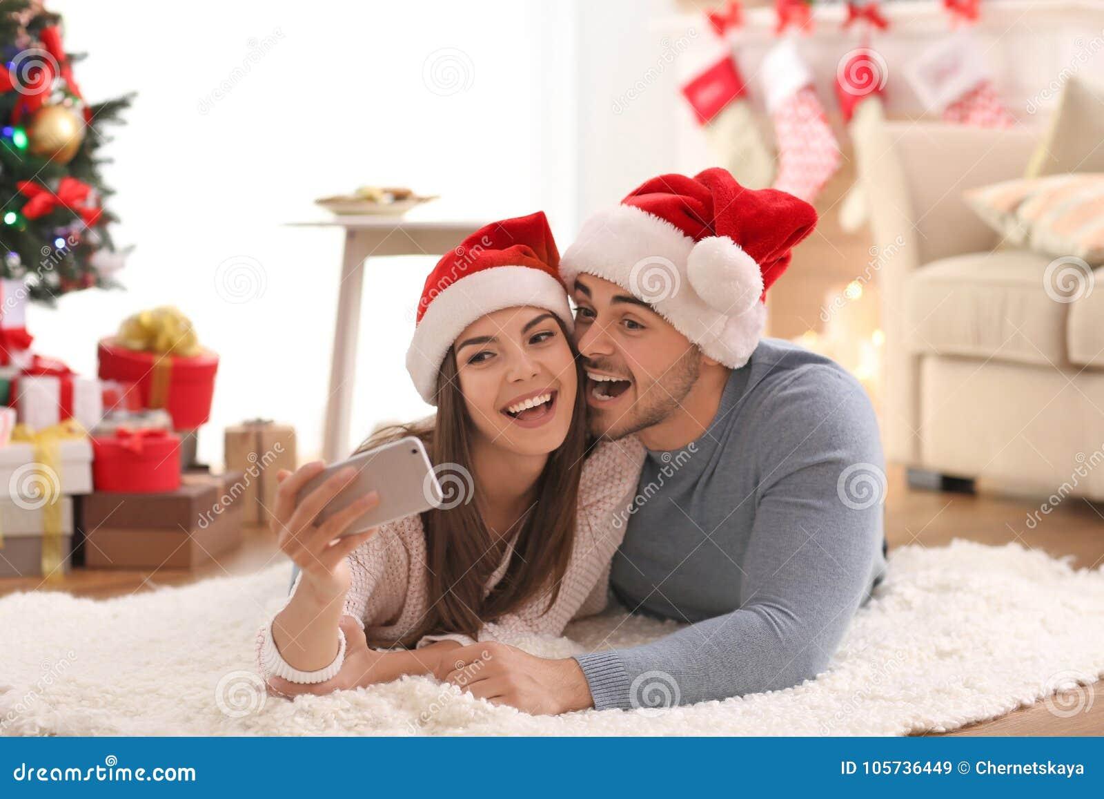 Pares jovenes en los sombreros de Santa Claus que hacen el selfie