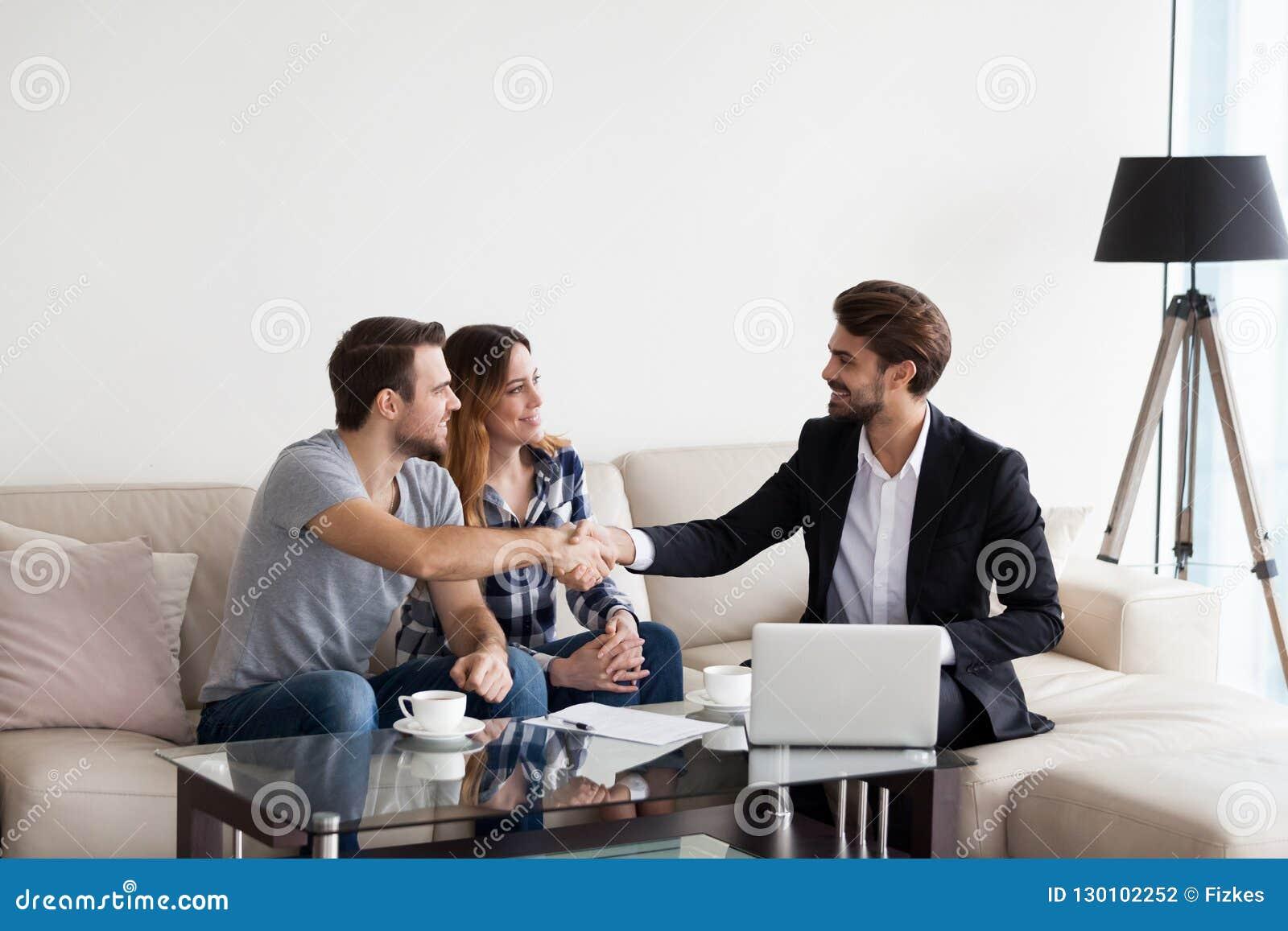 Pares jovenes, familia que hace trato con el agente inmobiliario, interiorista