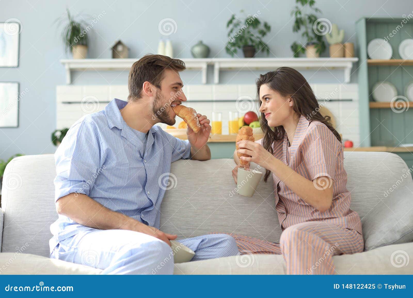Pares jovenes felices en pijamas en la cocina que desayuna, aliment?ndose un cruas?n