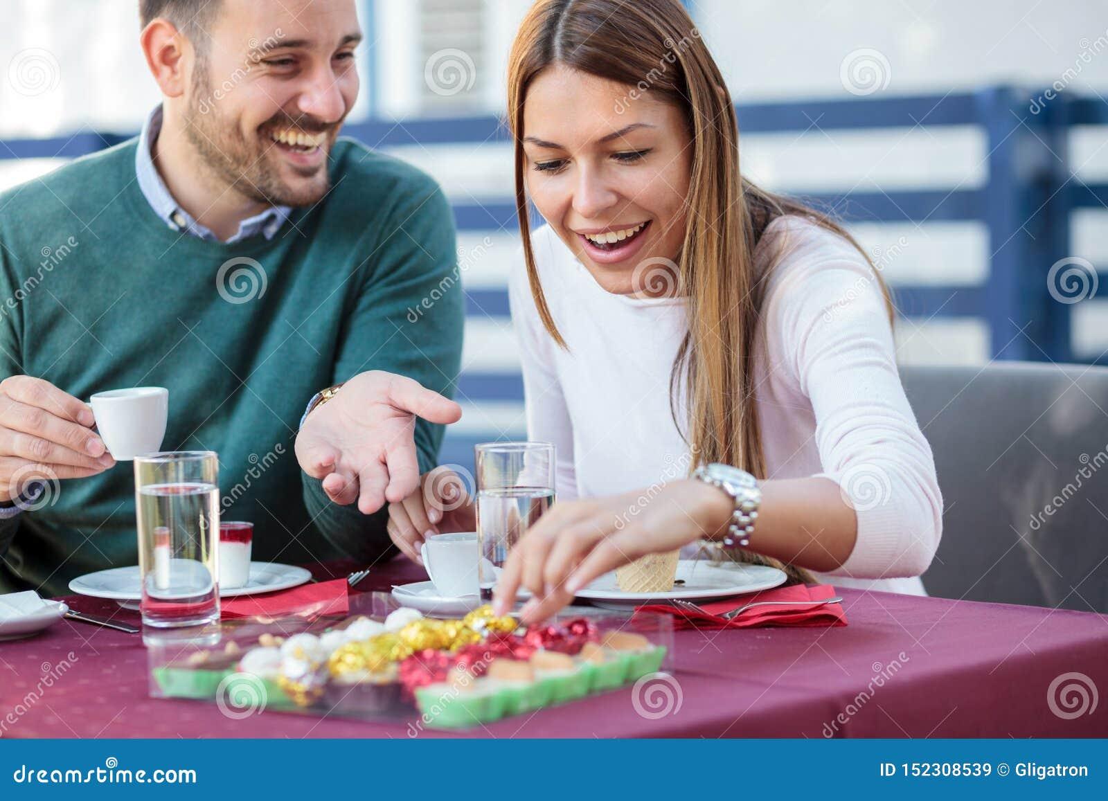 Pares jovenes felices hermosos que comen las tortas y que beben el café en un restaurante
