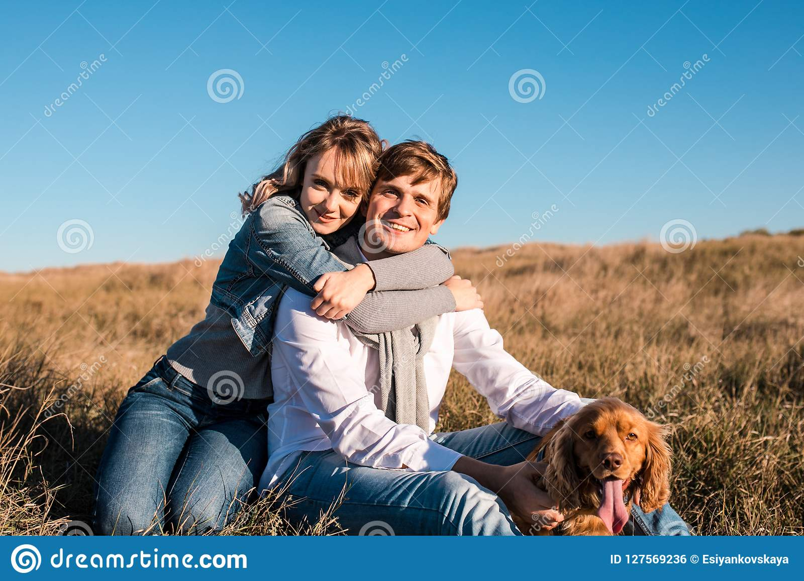 Pares jovenes felices que abrazan y que ríen al aire libre