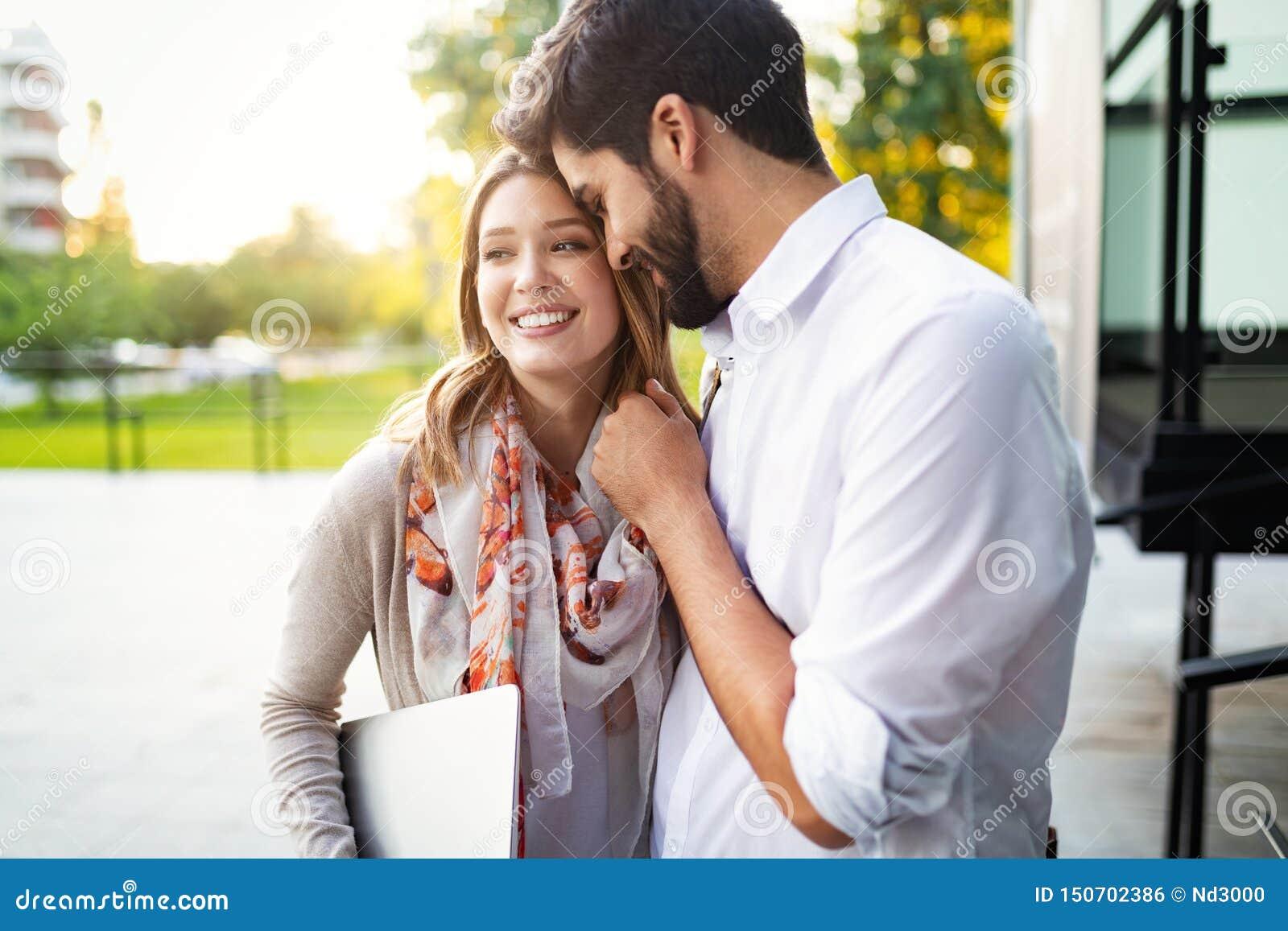 Pares jovenes felices que abrazan y que r?en al aire libre