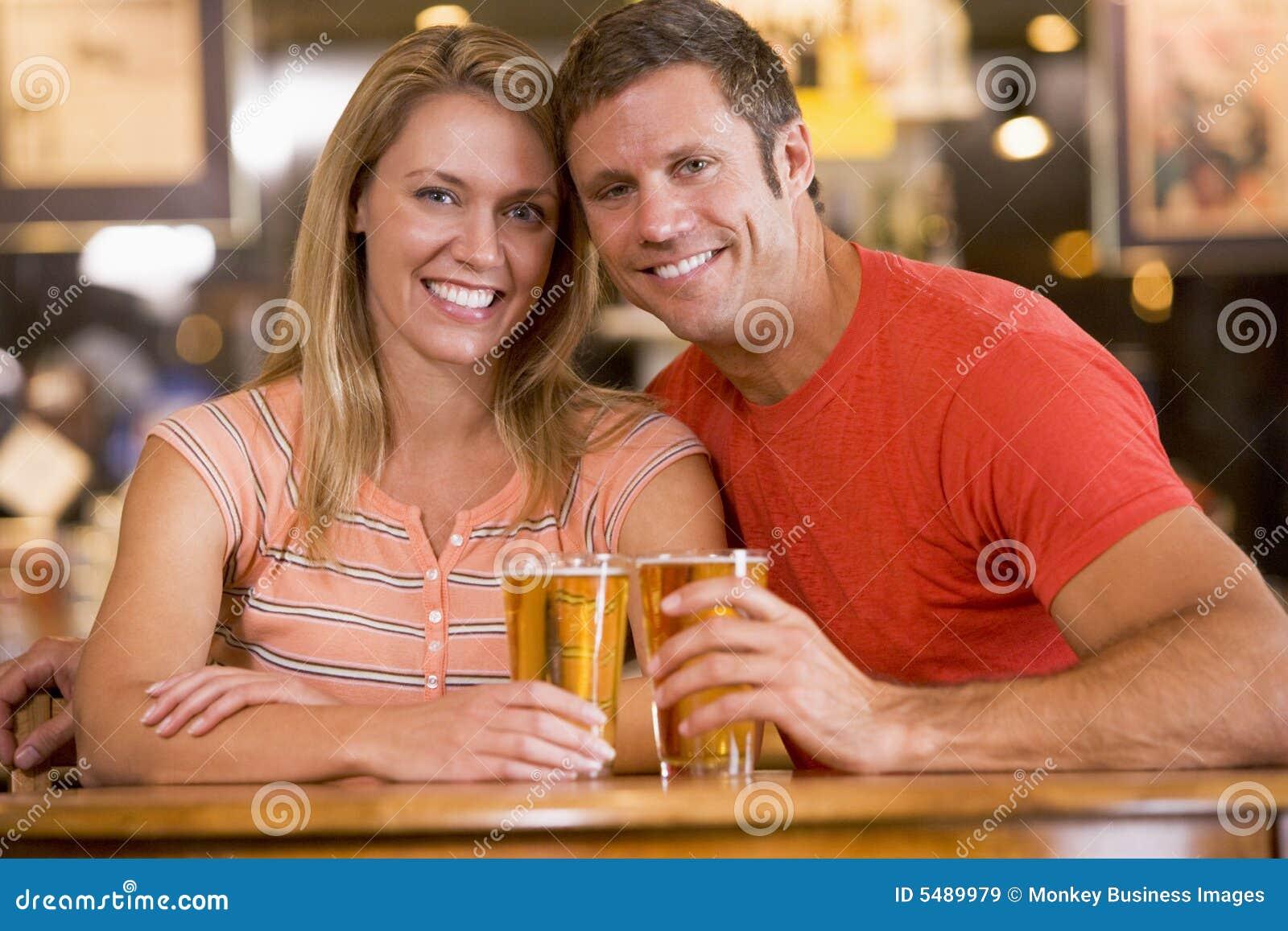 Pares jovenes felices que comen cervezas en una barra