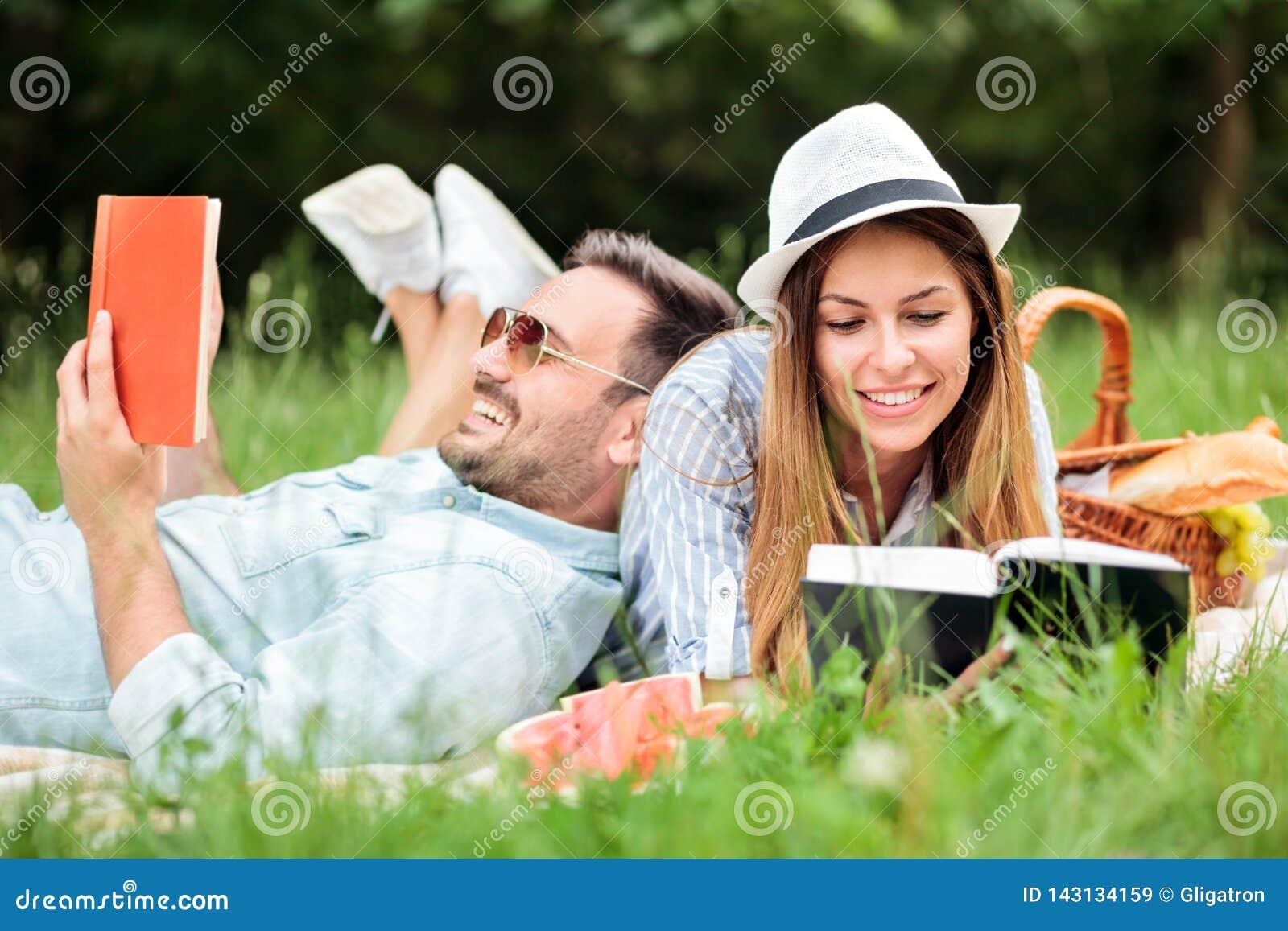 Pares jovenes felices que disfrutan de una buena lectura durante comida campestre en un parque