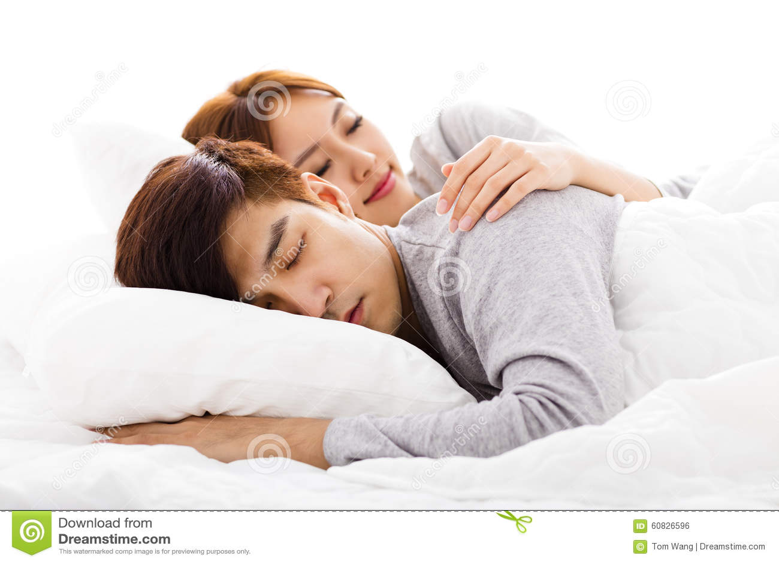 Pares jovenes felices que mienten en una cama
