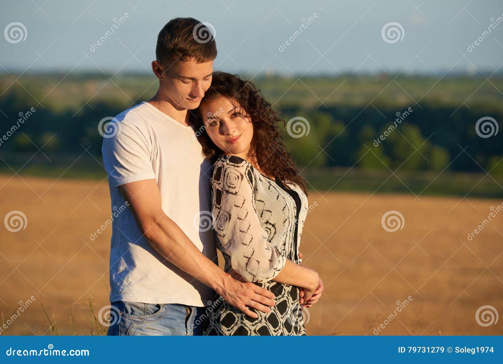 Pares jovenes felices que presentan arriba en el país al aire libre, concepto romántico de la gente, estación de verano