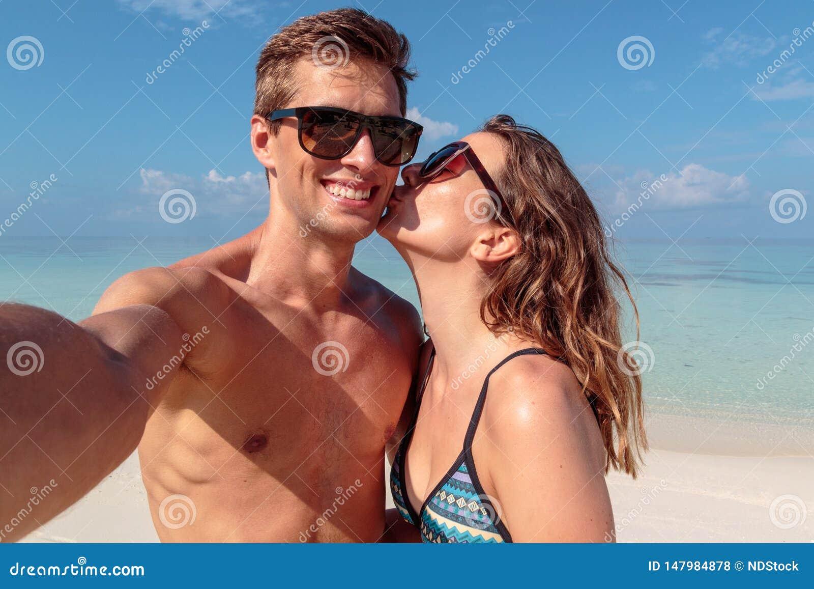 Pares jovenes felices que toman un selfie, agua azul clara como fondo Muchacha que besa a su novio