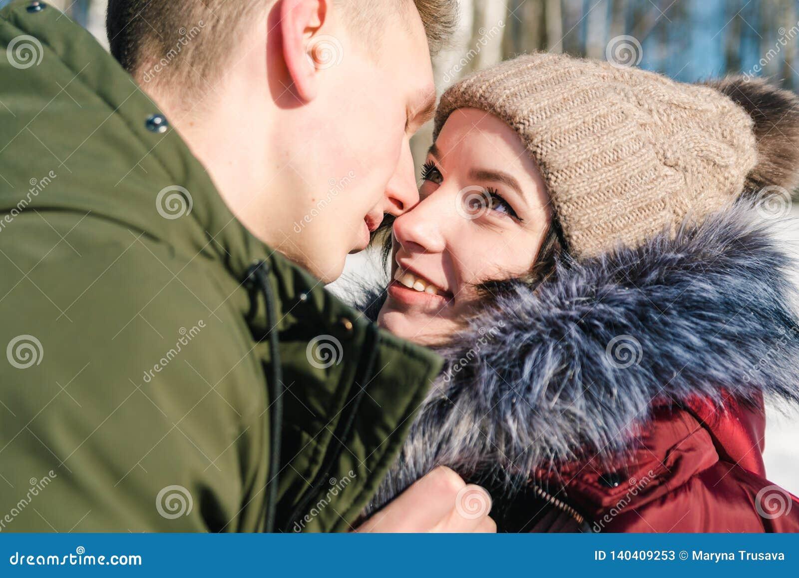 Pares jovenes hermosos en el amor que abraza en el parque en un día de invierno soleado claro, cierre para arriba Sonrisa del muc