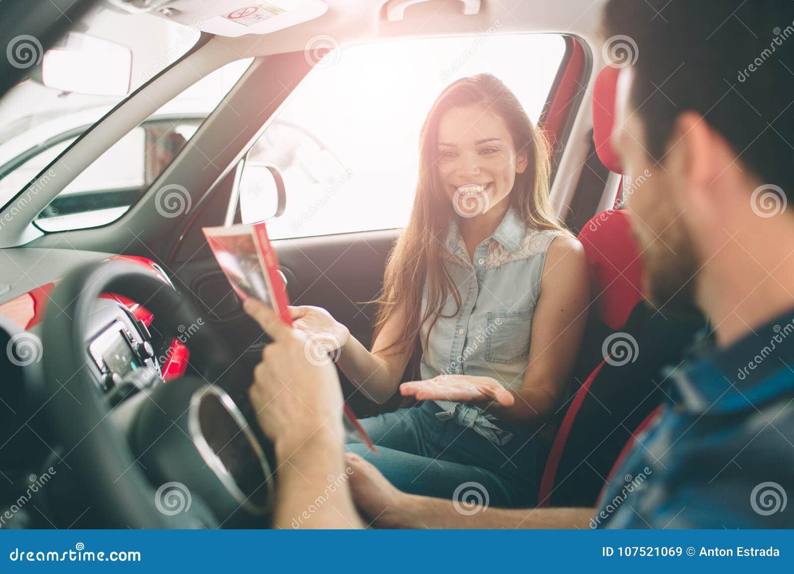 Pares jovenes hermosos que se colocan en la representación que elige el coche para comprar
