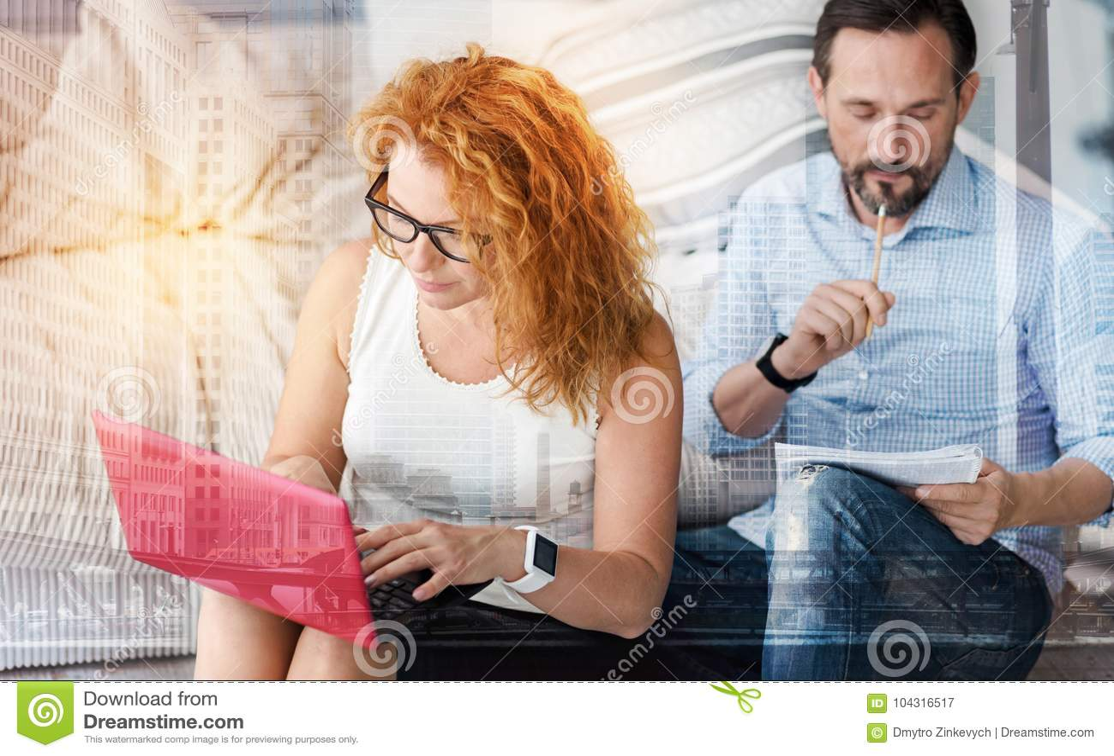 Pares jovenes ocupados que se sientan en casa junto y trabajo