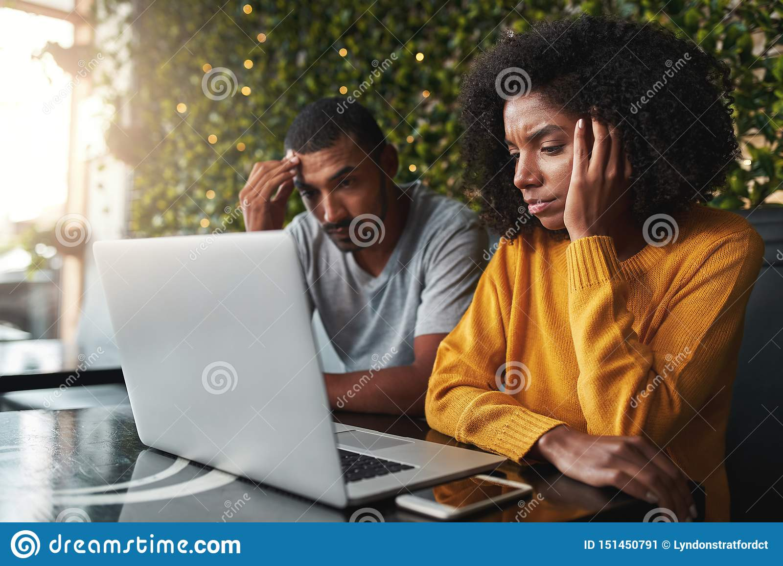 Pares jovenes preocupantes usando el ordenador portátil en café