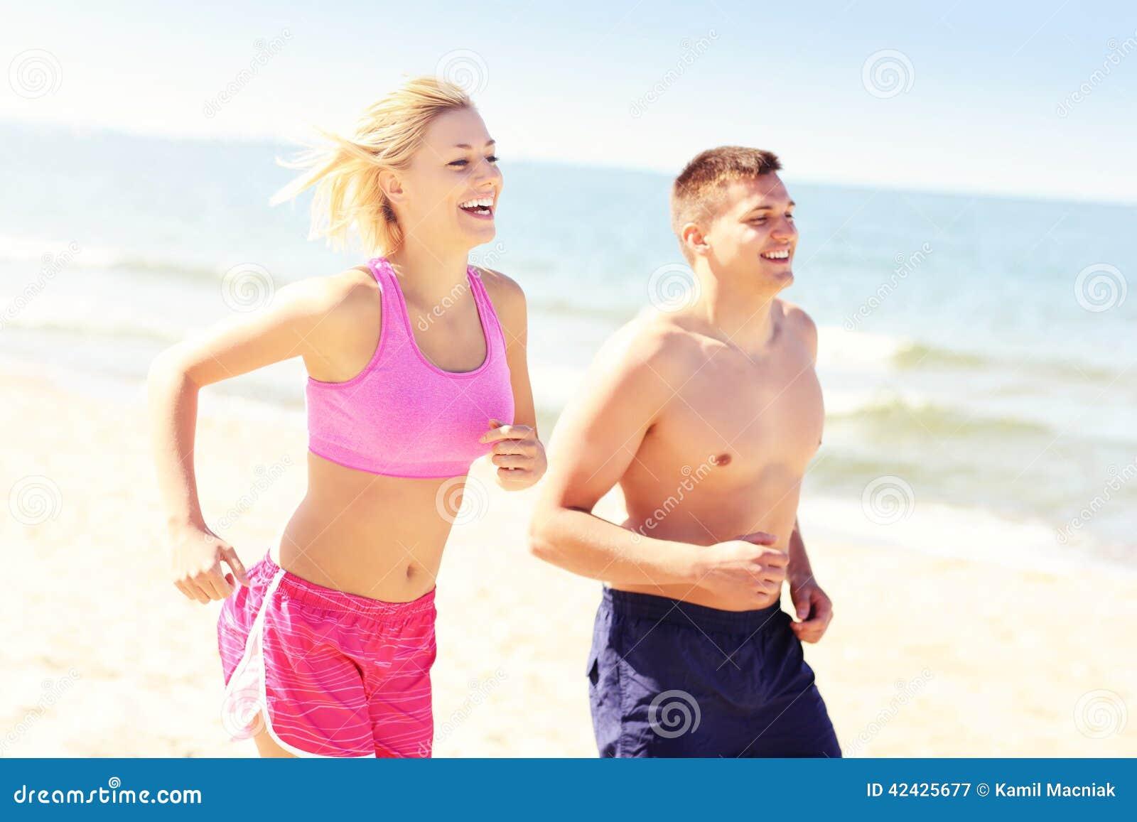 Pares jovenes que activan a lo largo de la playa