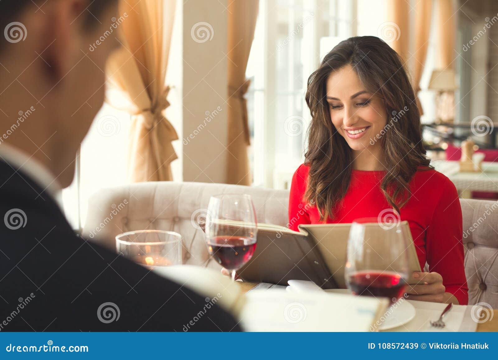 Pares jovenes que cenan romántico en el restaurante que lleva a cabo elegir del menú