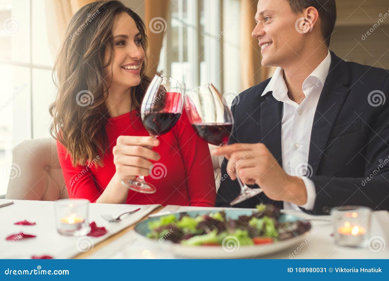 Pares jovenes que cenan romántico en el restaurante que se sienta junto llevando a cabo vista delantera de las copas de vino
