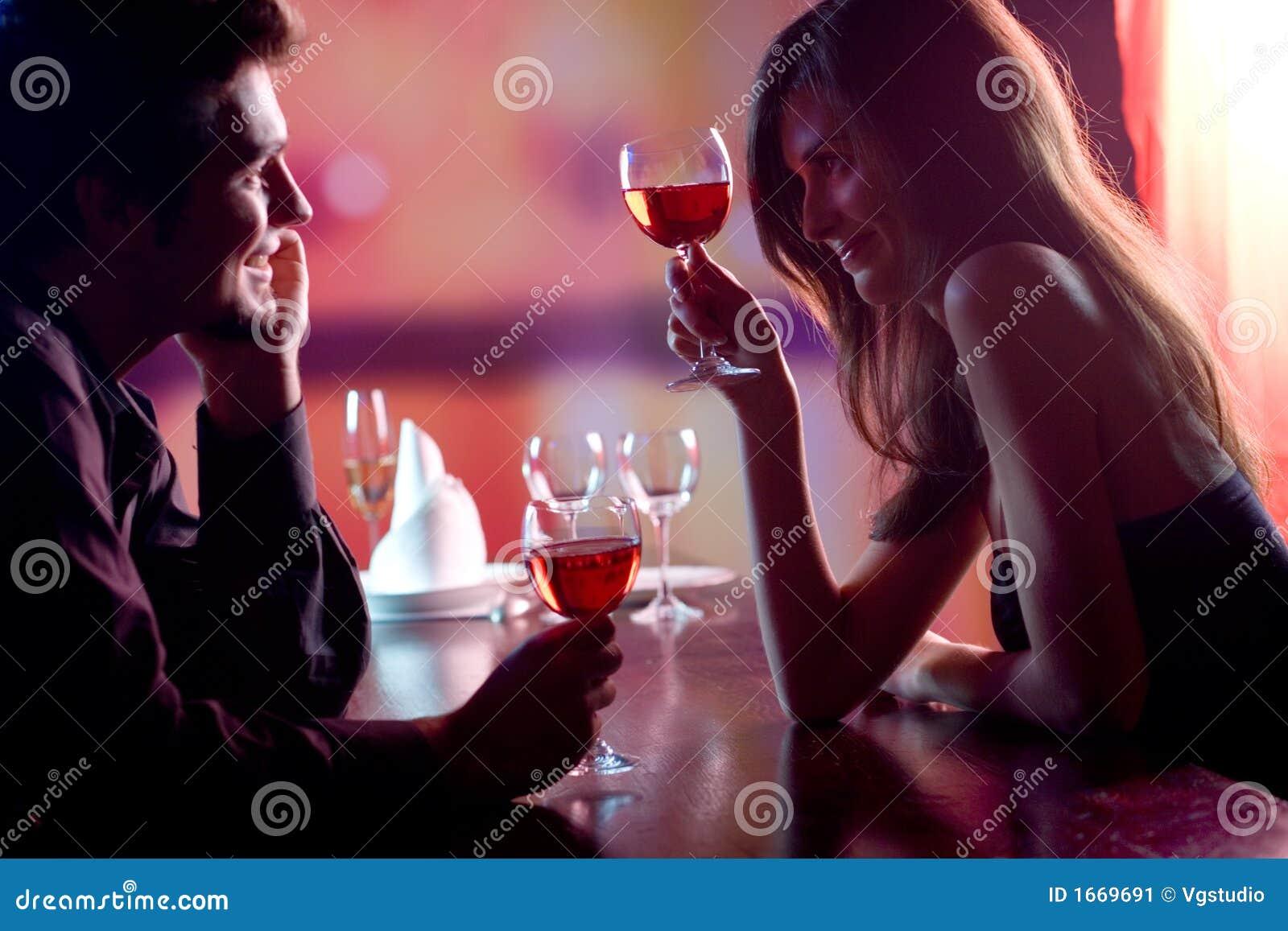 Pares jovenes que comparten un vidrio de vino rojo en el restaurante, celebrat