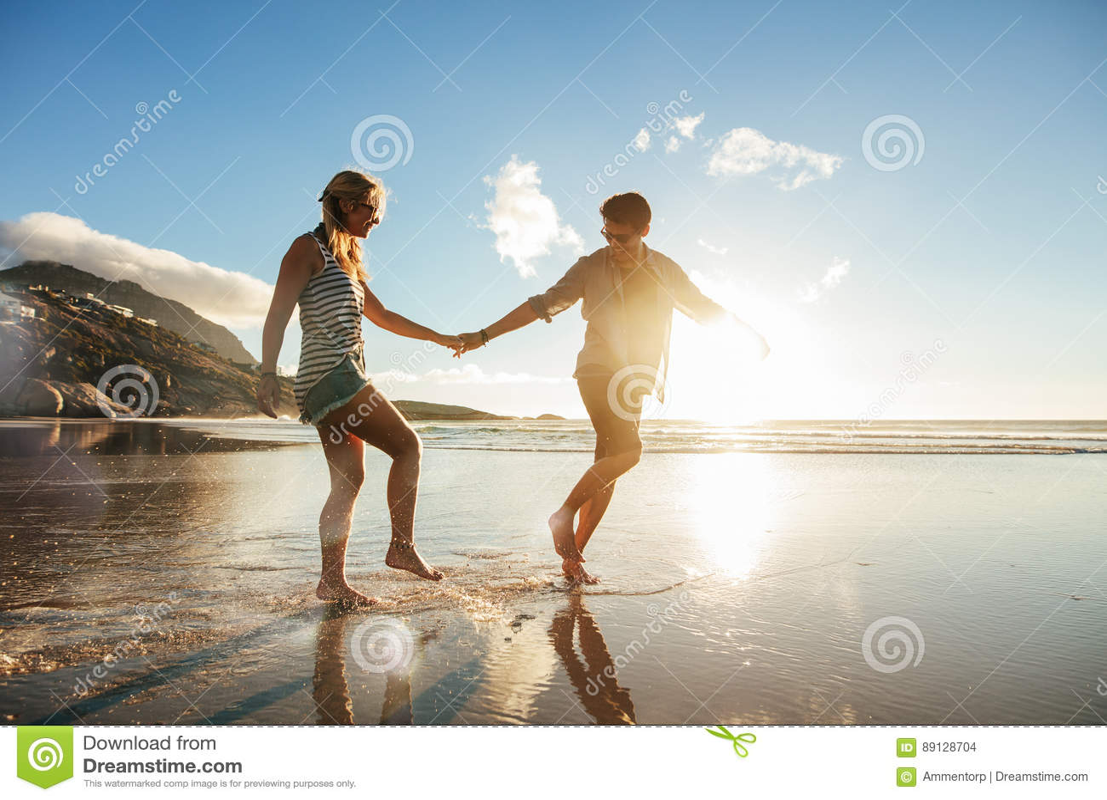 Pares jovenes que disfrutan de días de fiesta en la orilla de mar