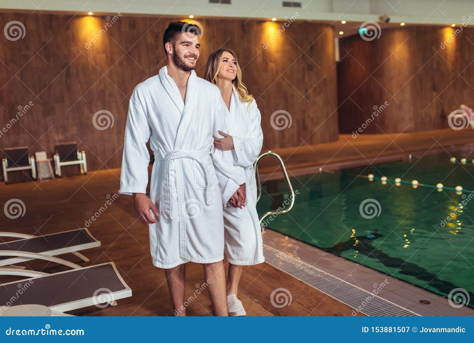 Pares jovenes que disfrutan de tratamientos y que se relajan en el centro del balneario de la salud