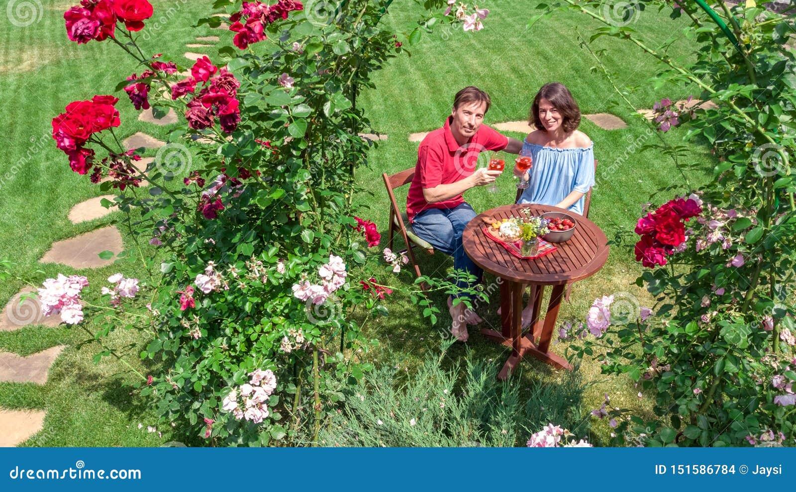 Pares jovenes que gozan de la comida y del vino en jardín de rosas hermoso en fecha romántica, la opinión superior aérea desde ar