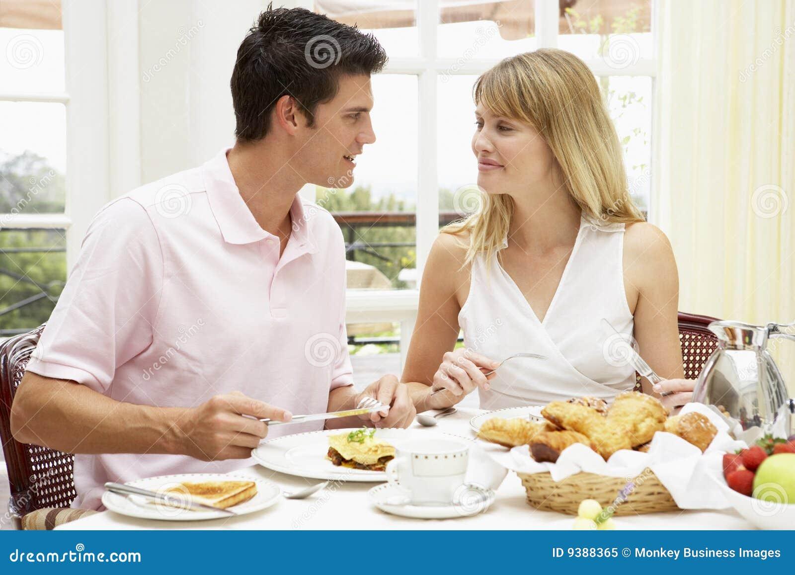 Pares jovenes que gozan del desayuno del hotel