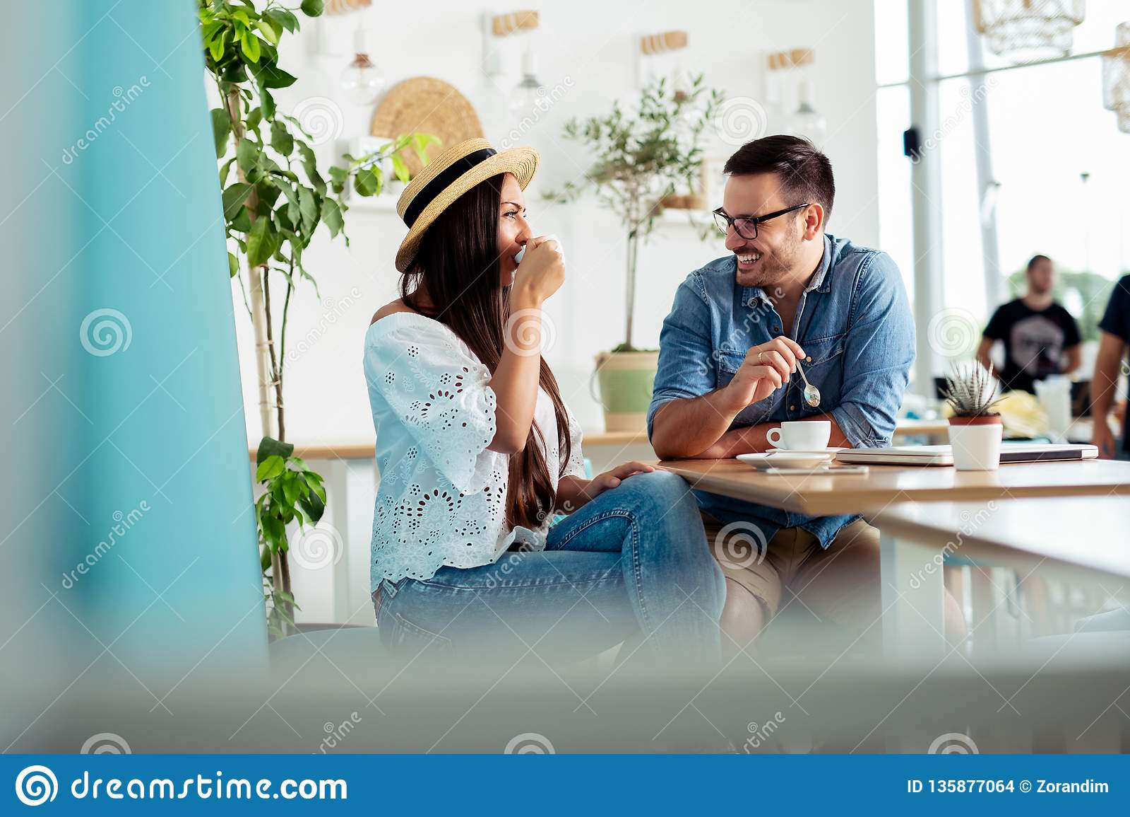 Pares jovenes que gozan del restaurante y que beben el café - Imagen