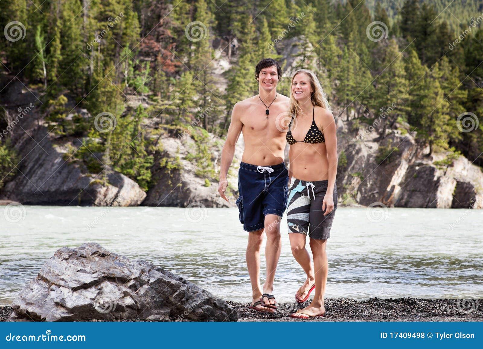 Pares jovenes que gozan por el lago
