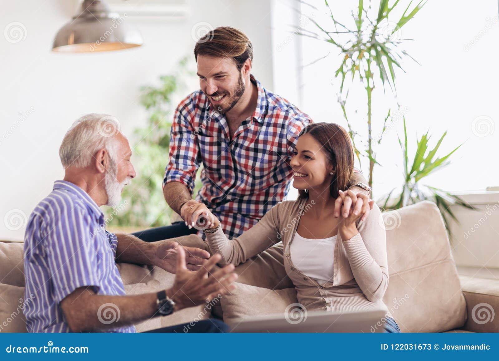 Pares jovenes que hablan con su padre mayor
