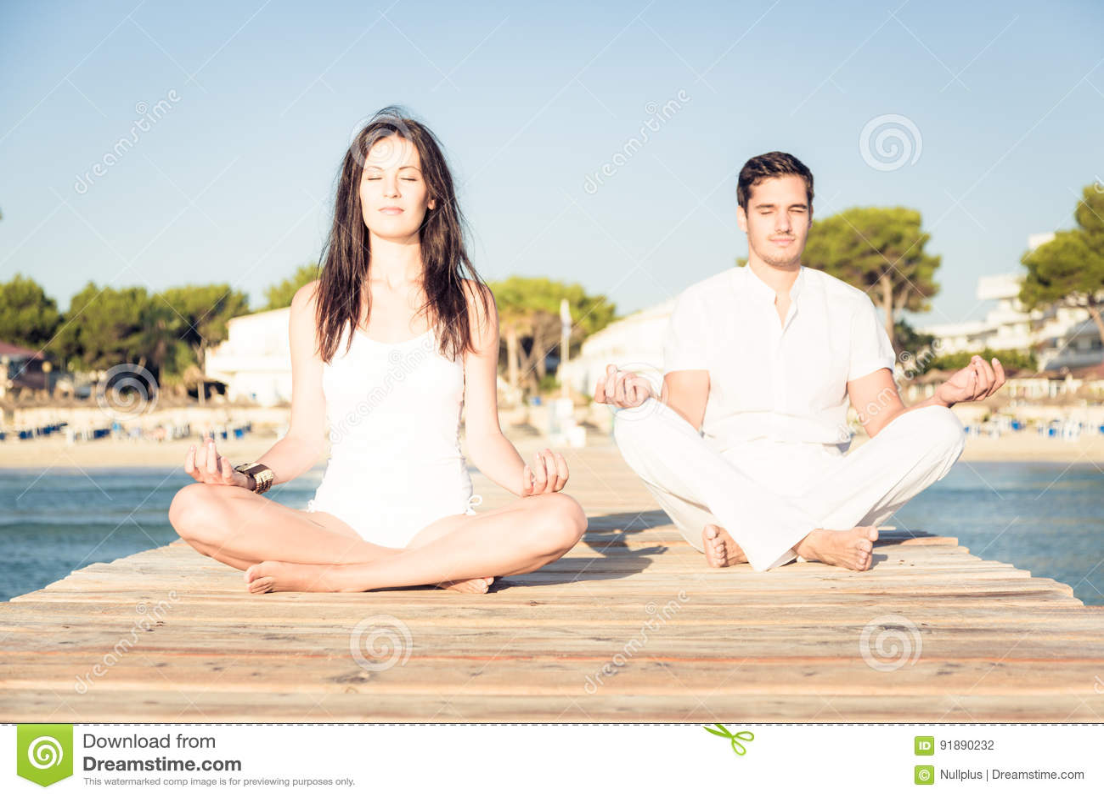 Pares jovenes que hacen yoga en el embarcadero