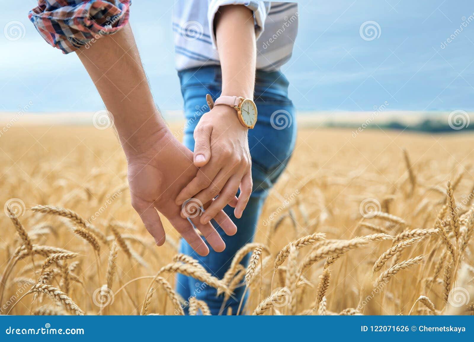 Pares jovenes que llevan a cabo las manos en campo de grano