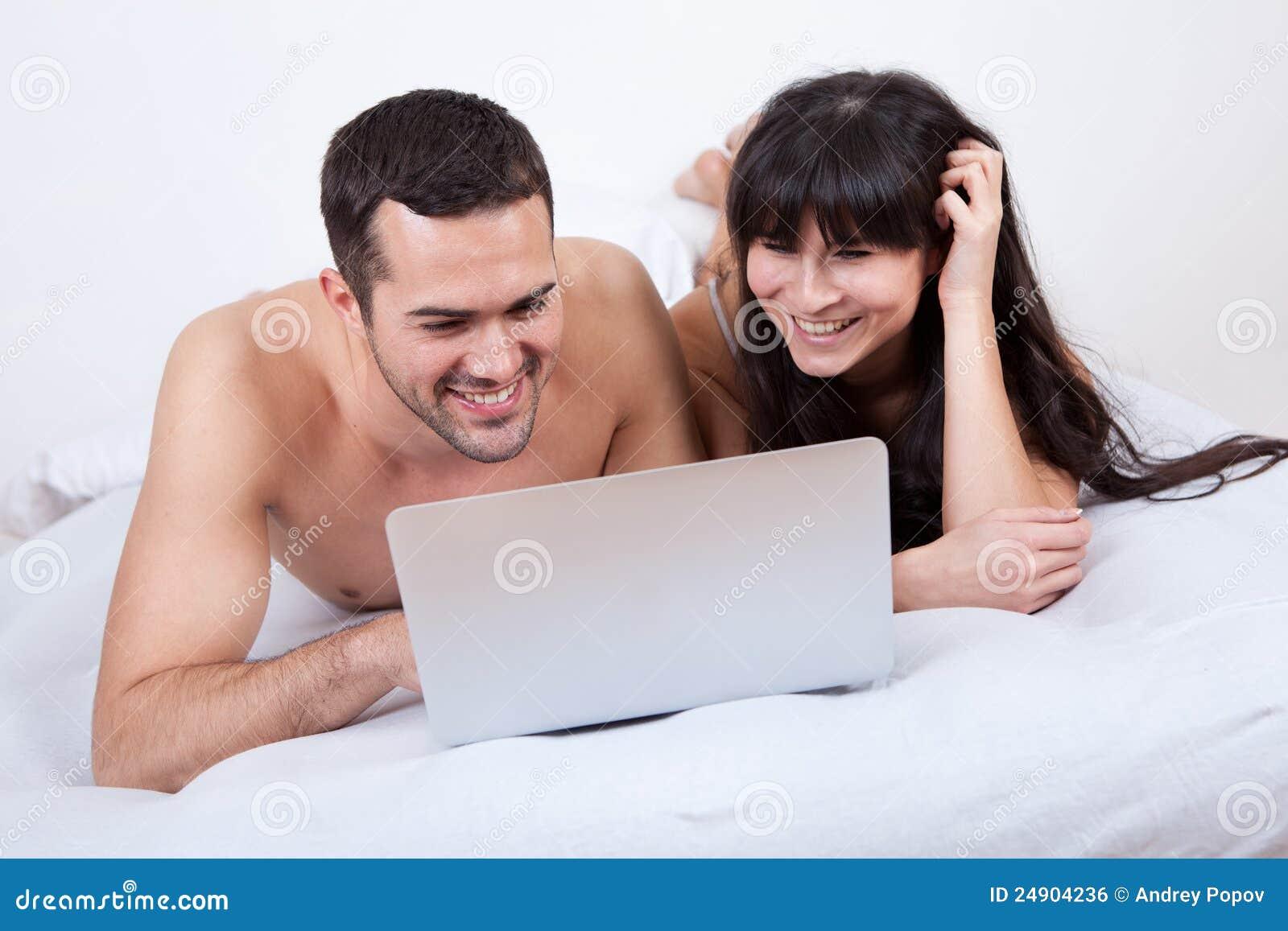 Pares jovenes que mienten para arriba en cama con la computadora portátil