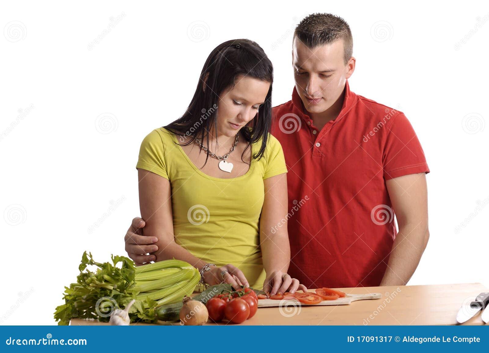 Pares jovenes que preparan la cena