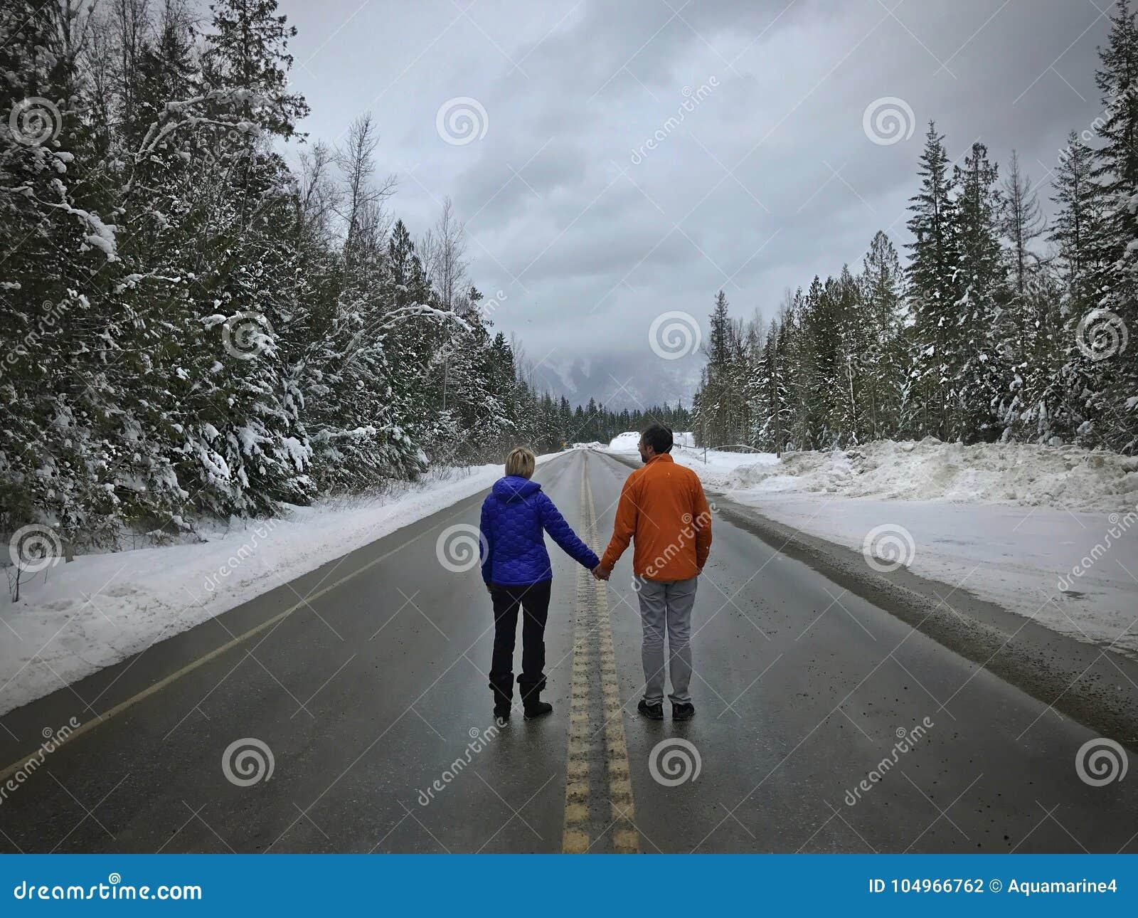 Pares jovenes que se colocan en el camino que lleva a cabo las manos Recienes casados cerca de Revelstok Columbia Británica canad