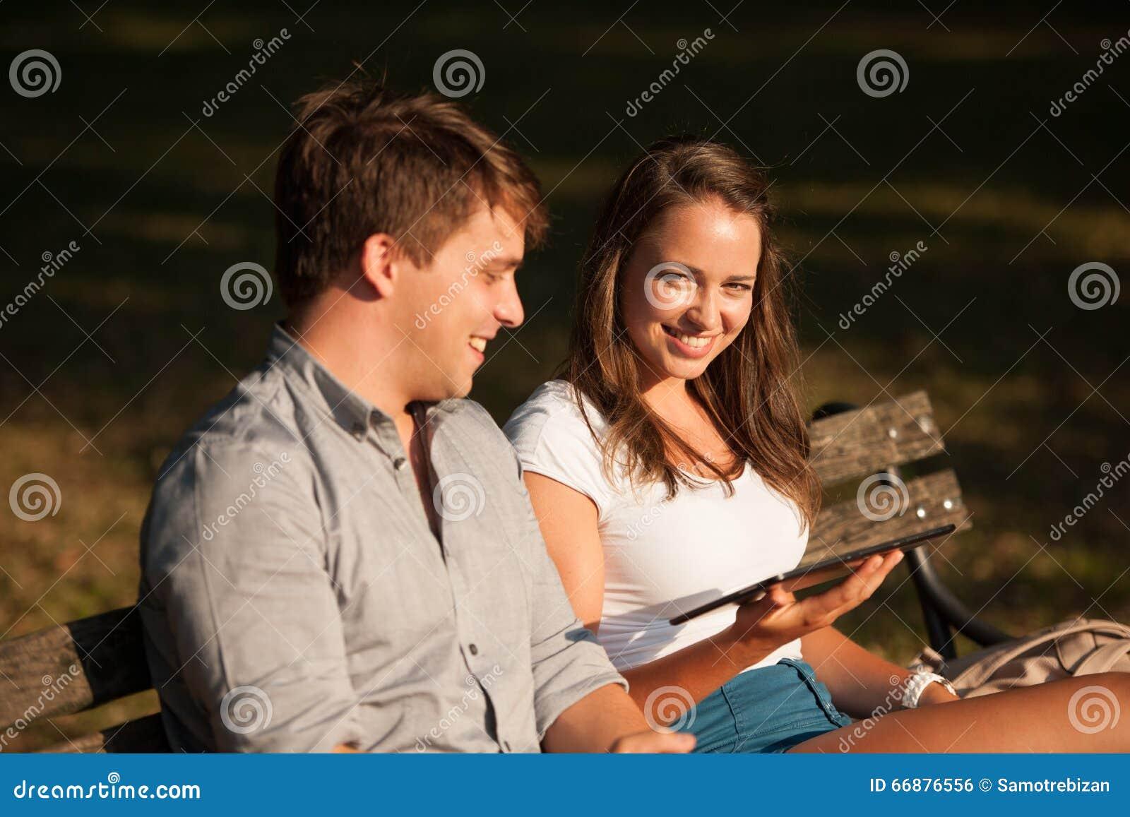 Pares jovenes que se divierten en un banco en parque mientras que socializa el ove