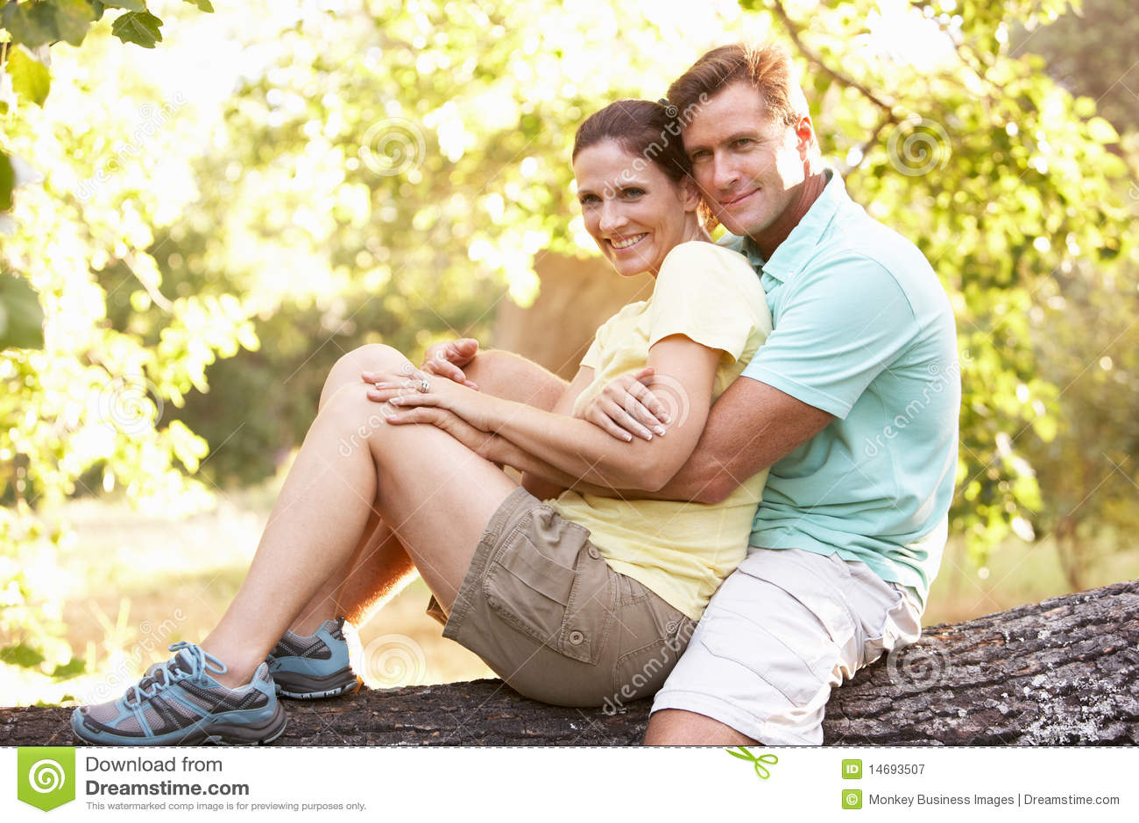 Pares jovenes que se reclinan sobre árbol en parque