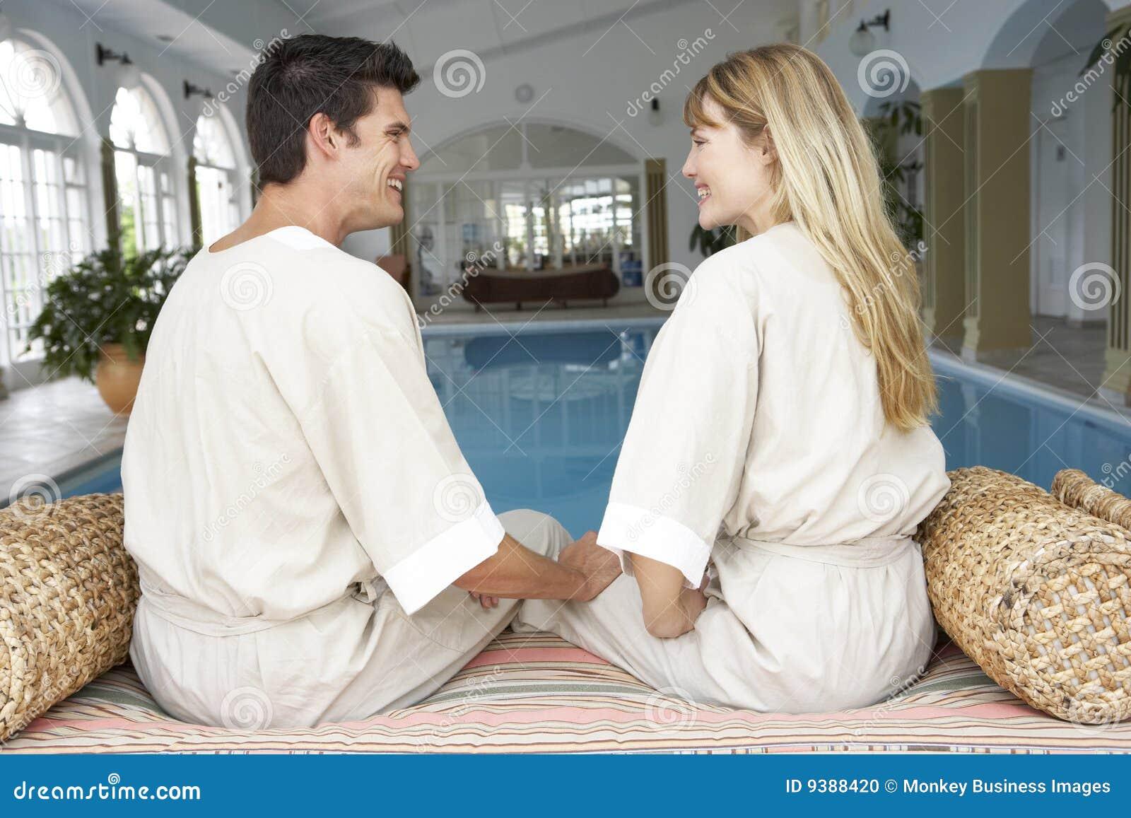 Pares jovenes que se relajan por la piscina