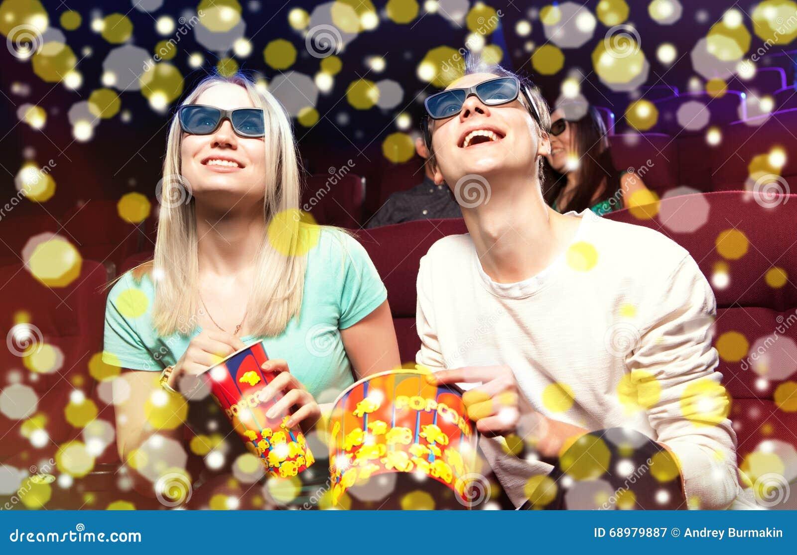 Pares jovenes que se sientan en el cine, mirando una película