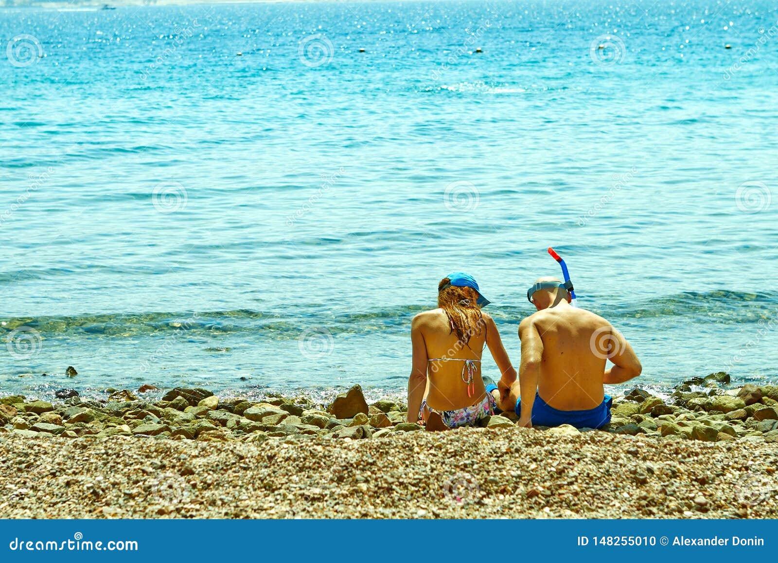 Pares jovenes que se sientan en la orilla del Mar Rojo